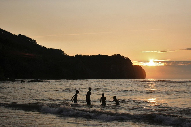 Boys jumping in sea at sunset