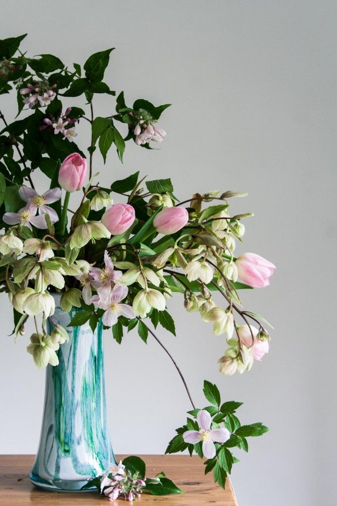 Spring floral arrangement featuring soft pink tulips, hellebores and clematis montana - Cloverhome.nl